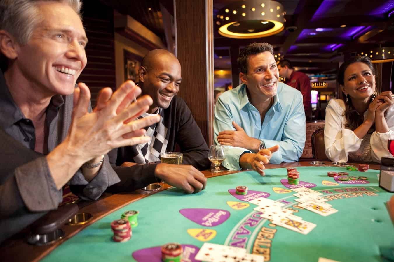 group of people being happy around a casino table