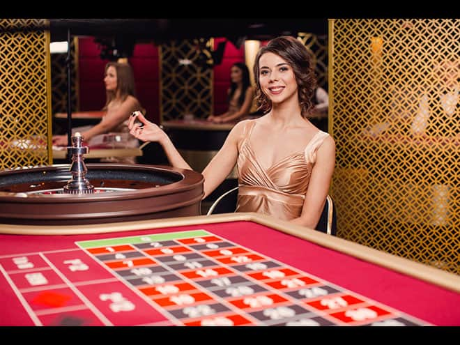 a roulette girl standing next to the roulette table